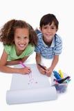 Portrait des amis de sourire dessinant tout en se trouvant sur le plancher Photos libres de droits