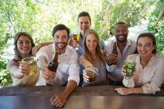 Portrait des amis de sourire montrant l'alcool au compteur Image libre de droits