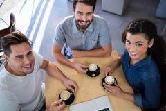 Portrait des amis de sourire s'asseyant à une table Photo stock