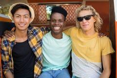 Portrait des amis de sourire s'asseyant au terrain de camping Image stock