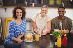 Portrait des amis de sourire s'asseyant avec la nourriture et la boisson au café Photographie stock
