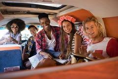 Portrait des amis de sourire s'asseyant dans le camping-car Image stock