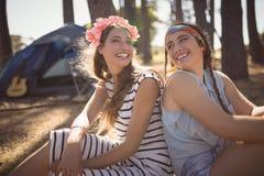 Portrait des amis de sourire s'asseyant sur le champ contre la tente Photos libres de droits