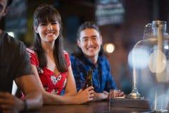 Portrait des amis de sourire se penchant au compteur Photo libre de droits