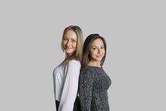 Portrait des amis de sourire se tenant de nouveau au dos sur le fond gris Image libre de droits