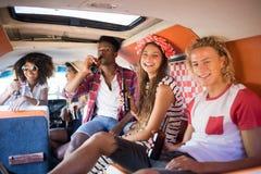 Portrait des amis de sourire tenant des bouteilles à bière ensemble dans le camping-car Image stock