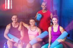 Portrait des amis de sourire tenant des tapis d'exercice Images stock