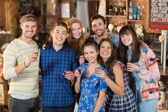 Portrait des amis de sourire tenant les verres courts Photographie stock