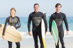 Portrait des amis de surfer avec la planche de surf se tenant sur la plage Image stock