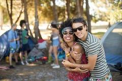 Portrait des amis embrassant au terrain de camping Photographie stock libre de droits
