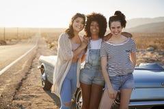 Portrait des amis féminins appréciant le voyage par la route se tenant à côté de la voiture classique sur la route de désert photo libre de droits