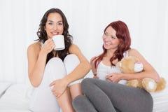 Portrait des amis féminins avec des tasses de café dans le lit Photographie stock libre de droits