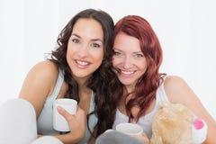 Portrait des amis féminins avec des tasses de café dans le lit Images stock