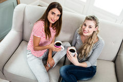 Portrait des amis féminins buvant du café sur le sofa Photographie stock libre de droits