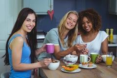 Portrait des amis féminins de sourire à l'aide du smartphone Photo libre de droits