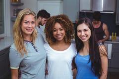 Portrait des amis féminins de sourire avec le bras autour Photo stock