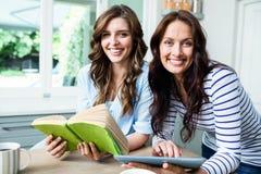 Portrait des amis féminins de sourire avec le livre et le comprimé numérique Photo stock