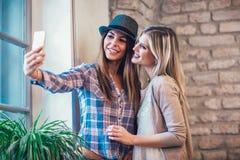 Portrait des amis féminins de sourire de jeunes à l'aide du téléphone intelligent Photo stock