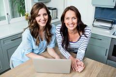 Portrait des amis féminins de sourire travaillant sur l'ordinateur portable Photographie stock libre de droits