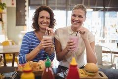 Portrait des amis féminins gais buvant du milkshake tout en se reposant au café Photographie stock