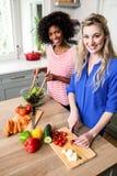 Portrait des amis féminins gais préparant la nourriture Photo stock