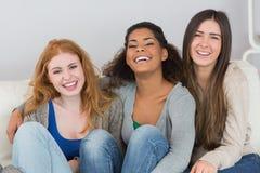Portrait des amis féminins gais s'asseyant à la maison Images libres de droits
