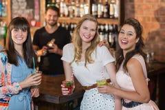 Portrait des amis féminins gais tenant des boissons dans la barre Photo stock