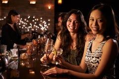 Portrait des amis féminins la nuit à la barre de cocktail Photo stock