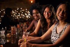 Portrait des amis féminins la nuit à la barre de cocktail Image stock