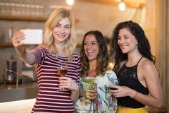 Portrait des amis féminins prenant le selfie tout en ayant des boissons Photographie stock libre de droits