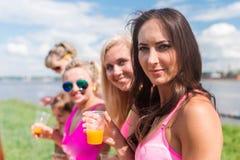 Portrait des amis féminins regardant l'appareil-photo smilling appréciant des vacances À l'extérieur pique-nique Photographie stock libre de droits