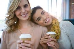 Portrait des amis féminins s'asseyant ensemble et ayant le café Images libres de droits