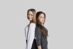 Portrait des amis féminins se tenant de nouveau au dos au-dessus du fond blanc Photo stock