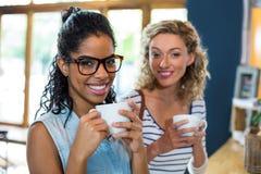 Portrait des amis féminins souriant tout en ayant le café Photos stock