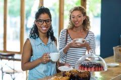 Portrait des amis féminins souriant tout en ayant le café Image stock