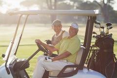 Portrait des amis gais de golfeur s'asseyant dans le boguet de golf Image stock