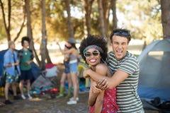 Portrait des amis gais embrassant au terrain de camping Images libres de droits