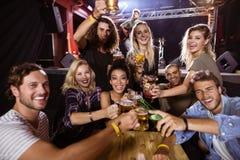 Portrait des amis gais grillant la boisson à la table avec l'interprète chantant sur l'étape Photographie stock libre de droits