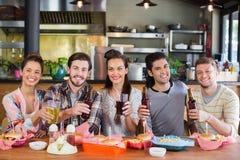 Portrait des amis gais tenant la bière dans le restaurant Photo stock