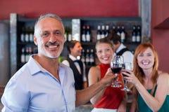 Portrait des amis grillant avec un verre de vin rouge dans une barre Image stock