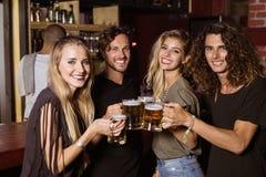 Portrait des amis grillant des verres de bière Photographie stock libre de droits