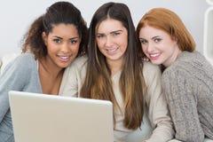 Portrait des amis heureux à l'aide de l'ordinateur portable ensemble sur le sofa Photos libres de droits