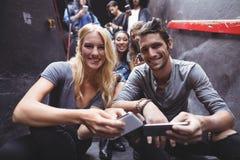 Portrait des amis heureux à l'aide des téléphones portables sur des étapes à la boîte de nuit Photos stock