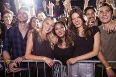 Portrait des amis heureux à la boîte de nuit pendant le festival de musique Photographie stock