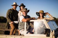 Portrait des amis heureux appréciant dans le véhicule pendant des vacances de safari Images libres de droits