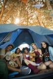 Portrait des amis heureux appréciant tout en se reposant dans la tente Photo libre de droits