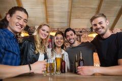 Portrait des amis heureux avec le verre et les bouteilles de bière Photo libre de droits