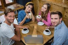 Portrait des amis heureux ayant le café à la table Images stock