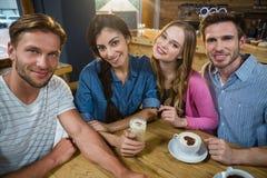 Portrait des amis heureux ayant le café Photos stock