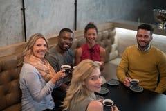 Portrait des amis heureux ayant le café Photographie stock